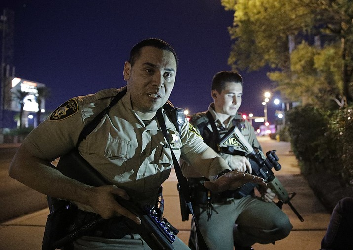 Police officers advise people to take cover near the scene of a shooting near the Mandalay Bay resort and casino on the Las Vegas Strip Sunday in Las Vegas.