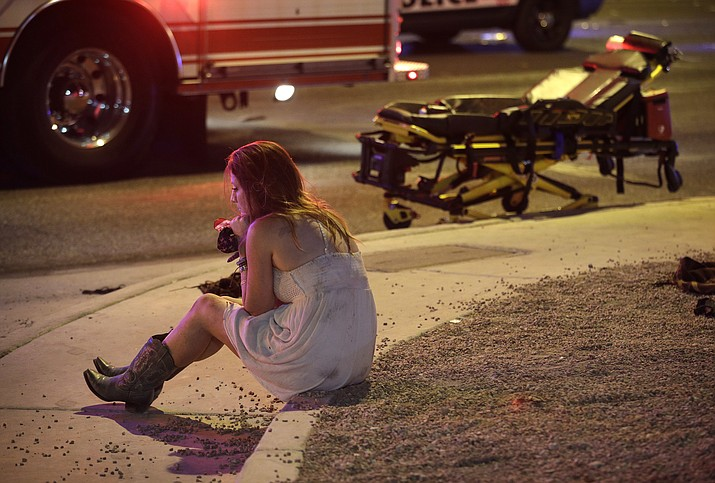 A woman sits on a curb at the scene of a shooting outside of a music festival along the Las Vegas Strip.  (John Locher/AP)