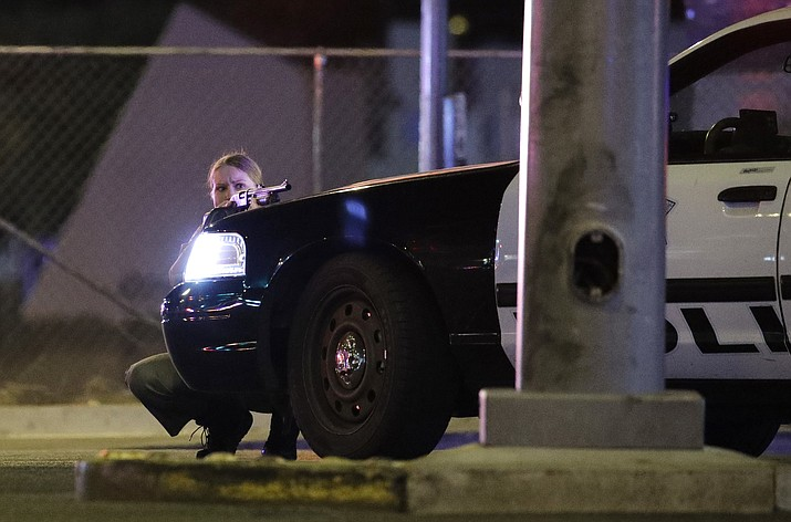 A police officer takes cover behind a police vehicle during a shooting near the Mandalay Bay resort and casino on the Las Vegas Strip late Sunday, Oct. 1, 2017, in Las Vegas. (John Locher/AP)