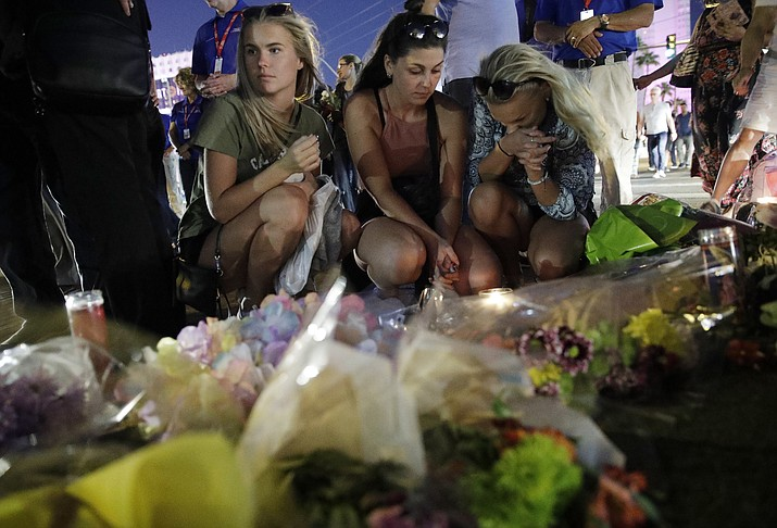 People pause at a memorial set up for victims of a mass shooting in Las Vegas, Nev., on Tuesday, Oct. 3, 2017. A gunman opened fire on an outdoor music concert on Sunday. It was the deadliest mass shooting in modern U.S. history, with dozens of people killed and hundreds injured, some by gunfire, some during the chaotic escape. (John Locher/AP)