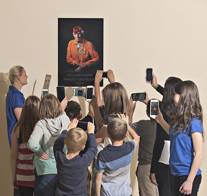 Lisa Pasalich, a teacher at Granville Elementary, instructs one of her classes to scan a donated portrait of a veteran using an application on their phones called Live Portrait. The technology blends augmented reality with image recognition to create images that come to life and tell a story. (Bruce Roscoe/Courtesy)