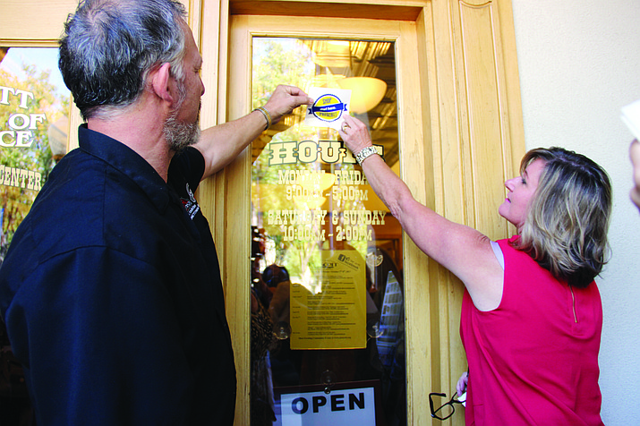 Prescott Chamber of Commerce Board Chairman Sanford Cohen and Chairman-Elect Margo Christensen paste the first Shop Prescott: Start Here sticker on the Prescott Chamber of Commerce's front door during a campaign launch event on Tuesday, Oct. 3. (Max Efrein/Courier)