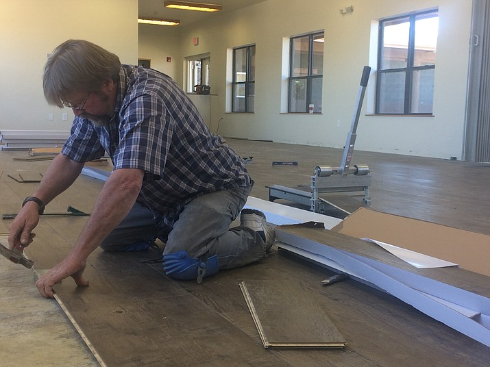Tim Davis of K T Interiors works on the floor of the Community Center where the Boys & Girls Club will be. (Jason Wheeler/Review)