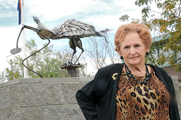 """Chino Valley artist Vivian Wells stands with her new metal sculpture, """"Patricia Paisano."""" The piece was installed as part of the Memory Park expansion project and rests between the park's current border and the Chino Valley Library. Depicting a mother roadrunner presenting food for her young ones, it is one of several Wells has planned for the expansion project. (Matt Santos/Courtesy)"""