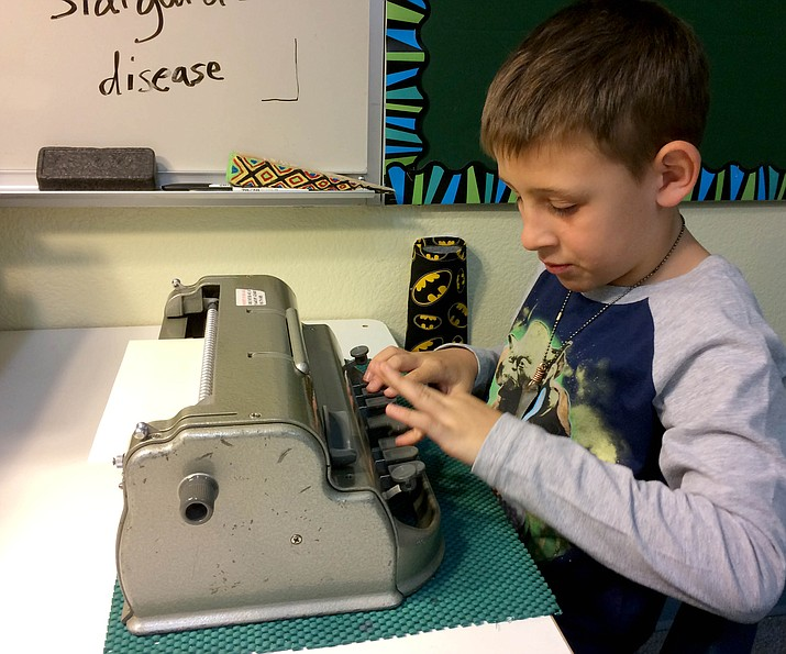 Coyote Springs Elementary School second-grader Logan Fischer demonstrates the manual Perkins Braille machine by typing out the alphabet. (Sue Tone/Tribune)