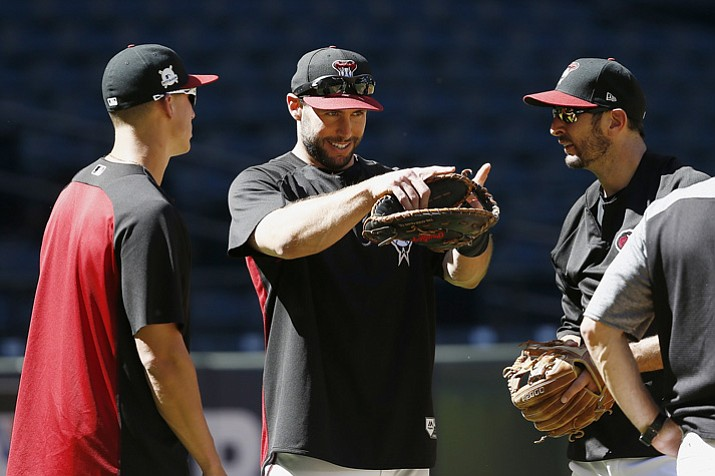 Arizona Diamondbacks third baseman Jake Lamb, left, first baseman Paul Goldschmidt, middle, and shortstop Adam Rosales, right, talk during practice at Chase Field as the team gets ready for a National League wildcard playoff game Monday, Oct. 2, 2017, in Phoenix. The Diamondbacks face the Colorado Rockies on Wednesday. (Ross D. Franklin/AP)