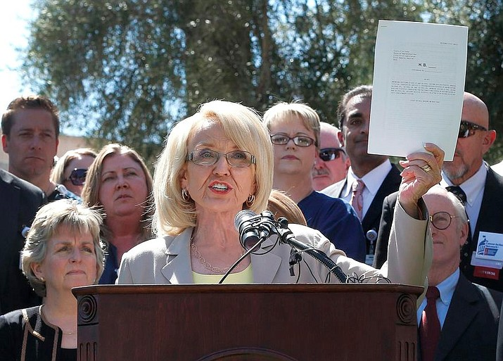 In this  March 12, 2014, file image, then-Arizona Gov. Jan Brewer holds a copy of the Medicaid Restoration Plan draft bill at the Capitol in Phoenix. (Matt York/AP, file)
