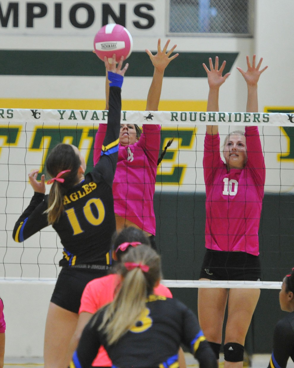 Yavapai's Kaytlin Yost (4) and Bailey Anderson (10) go up for a block on ERAU's Jalin Yoder (10) in the Battle Against Breast Cancer volleyball game Wednesday night at Yavapai College in Prescott. (Les Stukenberg/Courier)