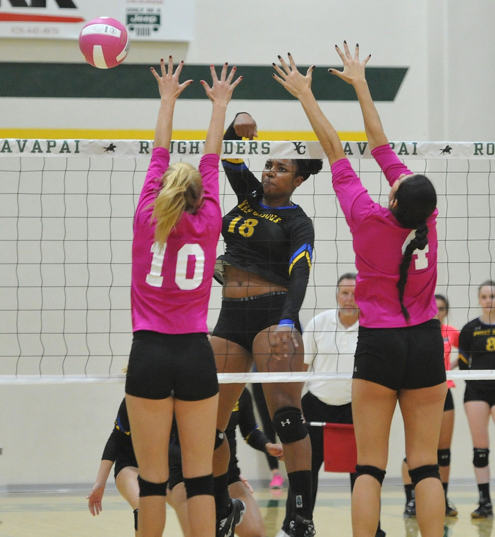 ERAU's Sharik Joseph (18) gets a kill on Yavapai's Bailey Anderson (10) and Kaytlin Yost (4) in the Battle Against Breast Cancer volleyball game Wednesday night at Yavapai College in Prescott. (Les Stukenberg/Courier)