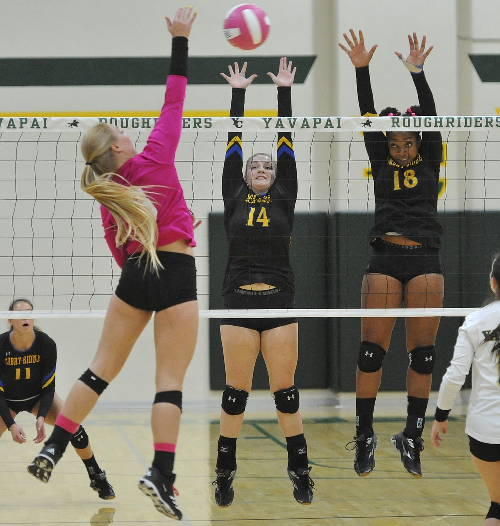 ERAU's Caylee Robalin (14) and Sharik Joseph (18) go for a block on Yavapai's Jaylinn Butler (3) in the Battle Against Breast Cancer volleyball game Wednesday night at Yavapai College in Prescott. (Les Stukenberg/Courier)