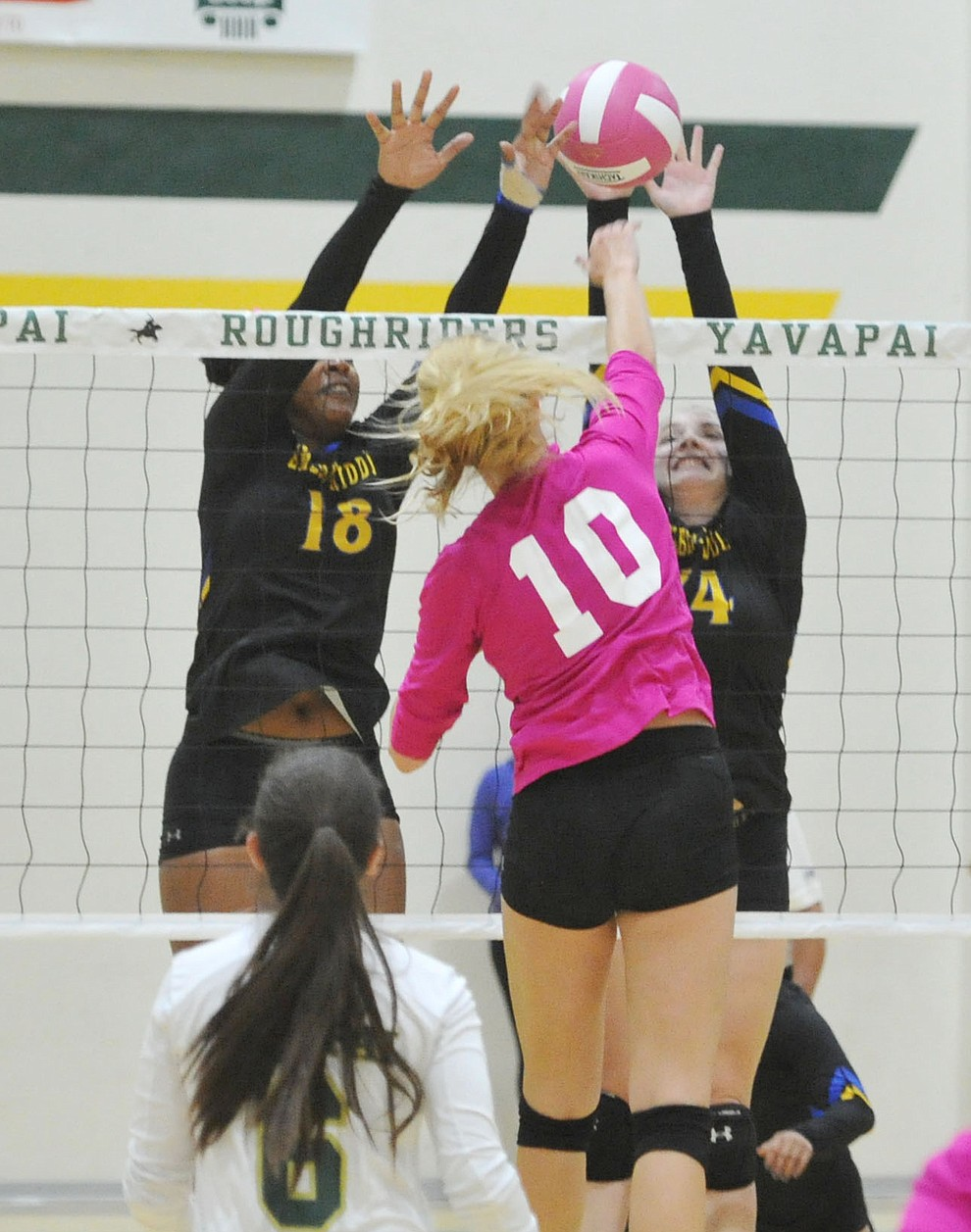 Yavapai's Bailey Anderson (10) gets a kill on ERAU's Sharik Joseph (18) and Caylee Robalin (14) in the Battle Against Breast Cancer volleyball game Wednesday night at Yavapai College in Prescott. (Les Stukenberg/Courier)