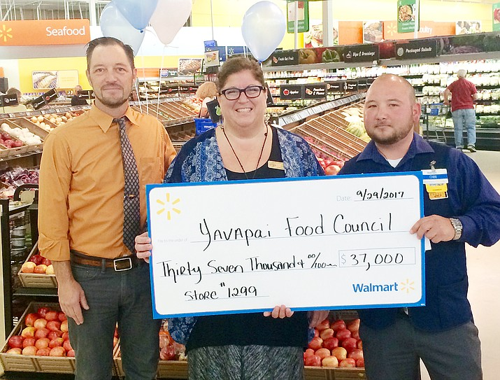 Cottonwood Walmart store Co-Manager Chris Quiroz, right, presents a $37,000 check to Yavapai Food Council's Executive Director Amy Aossey Friday morning to be used to fight hunger. Cottonwood Mayor Tim Elinski, pictured at left. (Courtesy photo)
