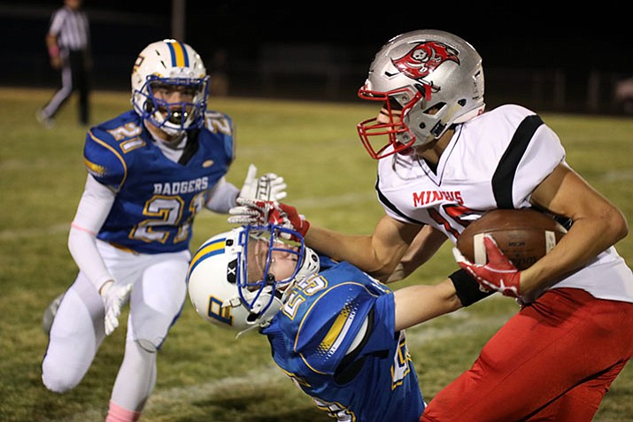 Mingus running back Alex Nelson bowls over Prescott defender Nick Robishaw (25) as Hunter Kronberg (21) comes in to help. The Badgers surrendered 447 yards on the ground defensively in a 38-6 loss to Mingus on Friday, Oct. 6, in Prescott.