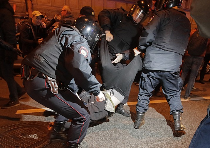 Riot police officers detain a protester during a rally in St.Petersburg, Russia, Saturday, Oct. 7. Supporters of opposition leader Alexei Navalny rallied across Russia, heeding his call to pressure authorities into letting him enter the presidential race with a wave of demonstrations on President Vladimir Putin's 65th birthday.