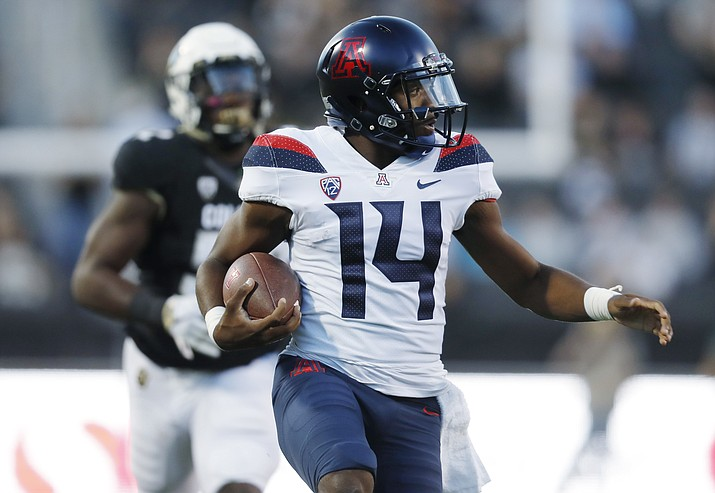 Arizona quarterback Khalil Tate, front, runs past Colorado defensive end Leo Jackson III on the way to a touchdown in the first half of an NCAA college football game. (David Zalubowski/AP)