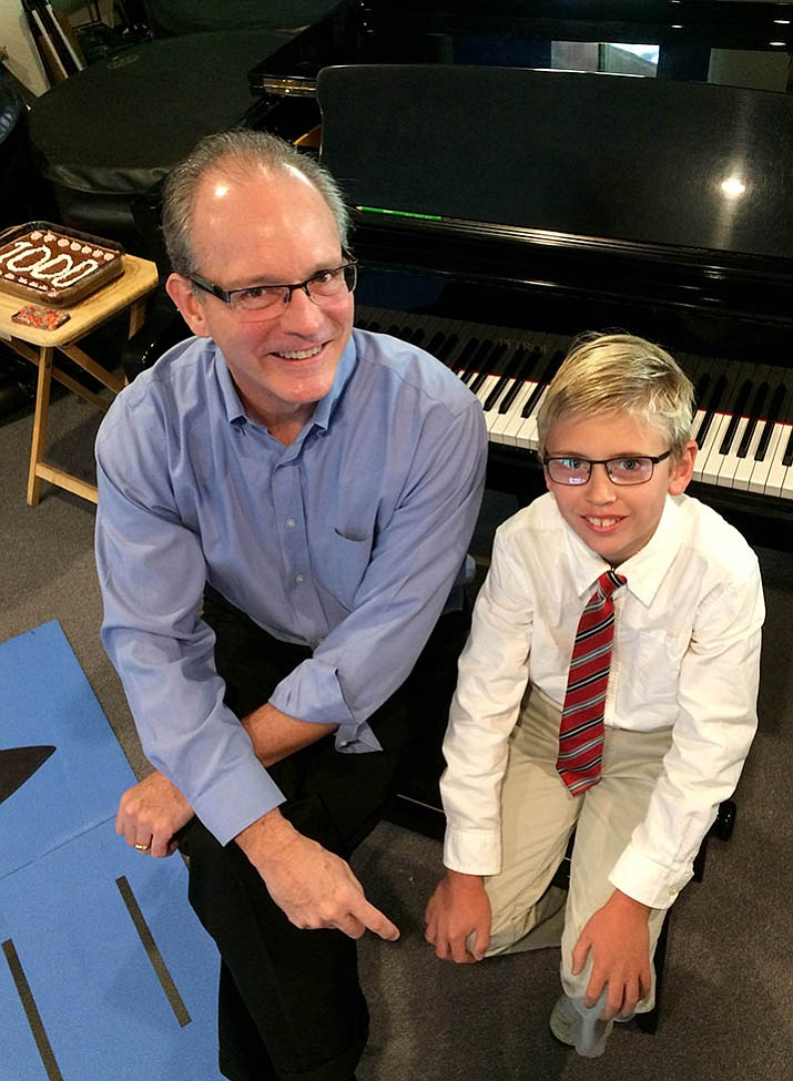 Matthew deGoey, 10, completed 1,000 days of piano practice on Sept. 30 after a 100-day challenge by instructor Henry Flurry, left, turned into 10 consecutive challenges lasting 2.75 years.