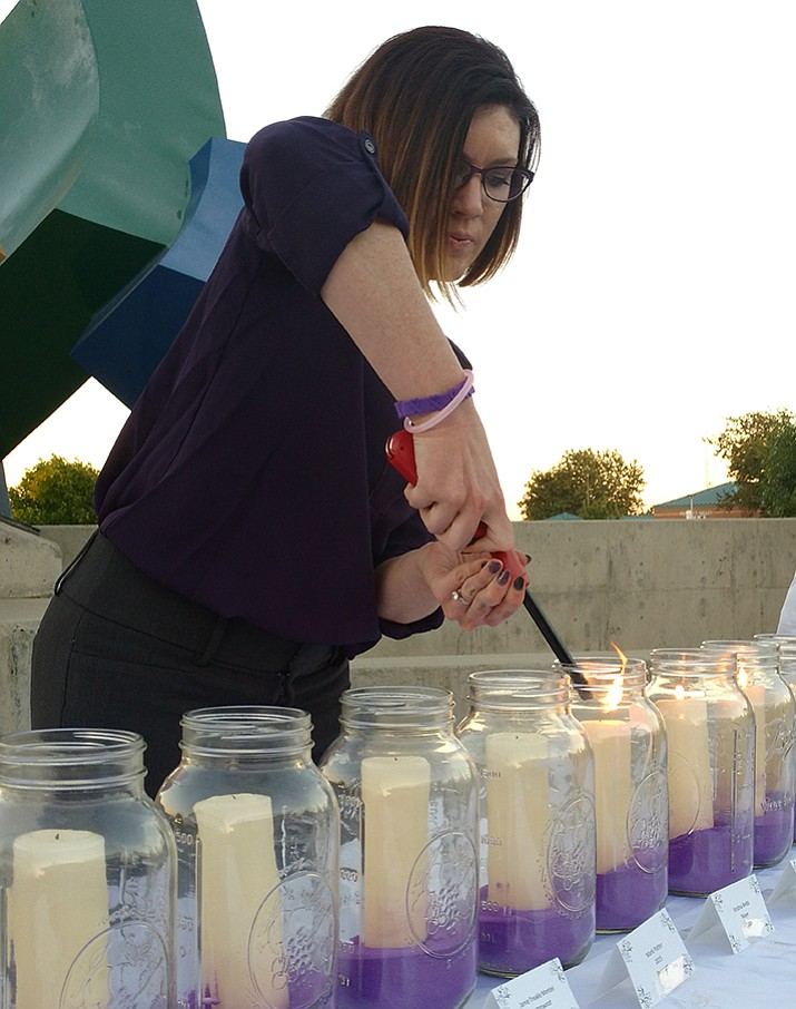 Jami Tiefenthaler lights candles in remembrance of Yavapai County domestic violence victims at a Take Back the Night event held Wednesday, Oct. 4, in Prescott Valley.