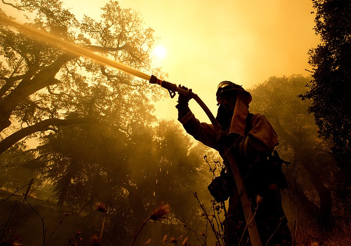 Napa County firefighter Jason Sheumann sprays water on a home as he battles flames from a wildfire Monday, Oct. 9, 2017, in Napa, Calif. Wildfires whipped by powerful winds swept through Northern California sending residents on a headlong flight to safety through smoke and flames as homes burned. (Rich Pedroncelli/AP)