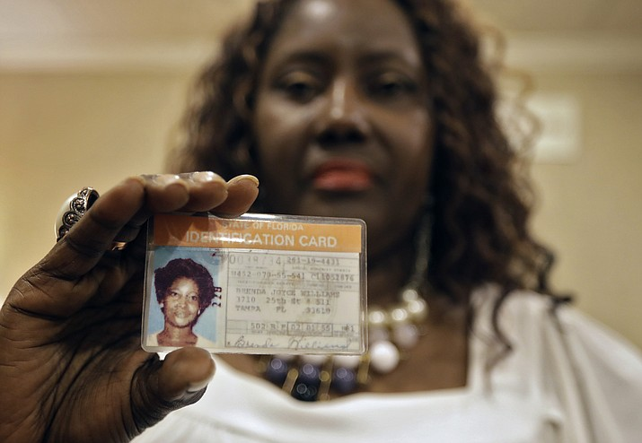 Sharon Scott poses for a photo with a Florida identification card for her missing sister Brenda Williams in Tampa, Fla. After decades of waiting to know what happened to their relative, Tampa Police officials told the family that they found a DNA match in a jawbone found in 1986. Williams, a young mother of two, went missing in 1978. (AP Photo/Chris O'Meara)
