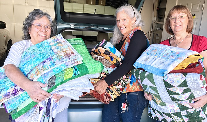 From left, Quail Country Quilters members Ruth Meyers, Karen Crowder and Mary Radtke prepare for the Oct. 13-14 Covey of Quilts show at Cottonwood Middle School. (Photo by Bill Helm)
