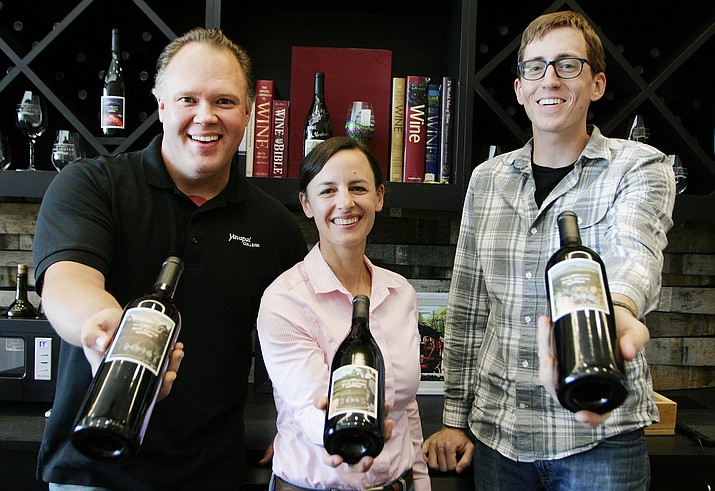 Philip Brown, Nikki Bagley and Michael Pierce, from left, of Yavapai College's Southwest Wine Center, show some of the many different types of wine produced by the program's students. Revenue from the program's Wine Tasting Room exceeded forecasts for the fiscal year by more than 30 percent. (Photo by Bill Helm