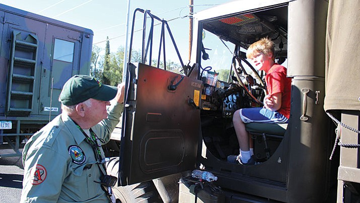 Justin D'Antonio, 10, sits in the cab of a 1970 MB35 military truck and asks questions of owner Gilbert Jeane of Arkansas.