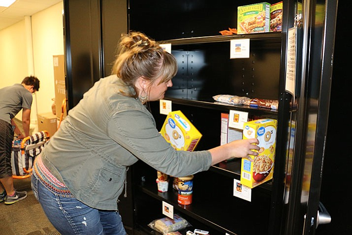 A member of Yavapai College's student-run philanthropy club I Am YC stocks the shelves of Yavapai College's brand-new emergency food pantry. (J.J. McCormack/Courtesy)
