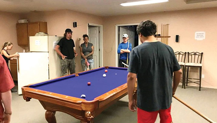 A group of young men played pool as a volunteer watched Thursday at the Kingdom Of God Church's youth group, where a new youth center will be opening in November.
