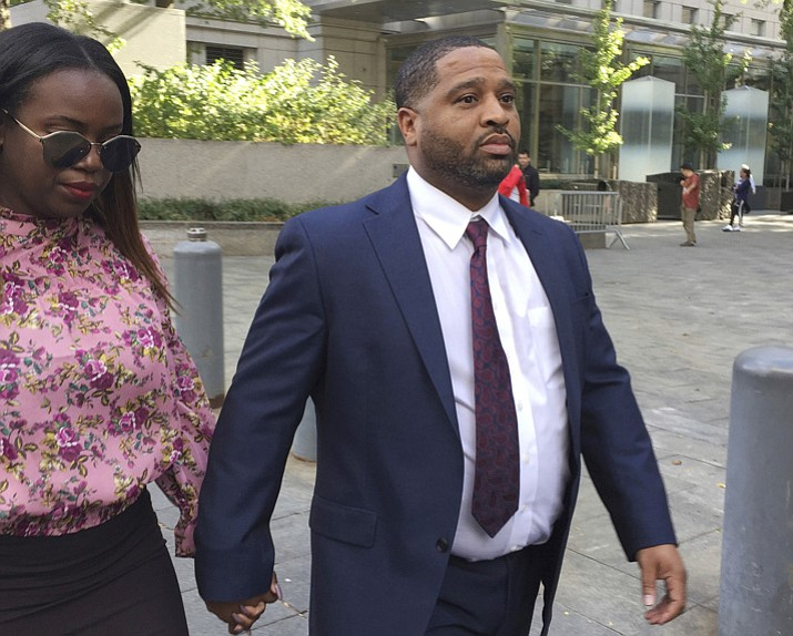 Suspended University of Arizona assistant men's basketball coach, Emanuel Richardson, leaves Manhattan federal court Tuesday, Oct. 10, 2017, in New York, after an initial appearance before a magistrate judge. Richardson will remain free on $100,000 bond. He awaits trial along with three other coaches in a case in which the coaches and others are charged with using hundreds of thousands of dollars in bribes to influence the choices star athletes make about schools, sponsors, agents and financial advisers. (Larry Neumeister/AP)