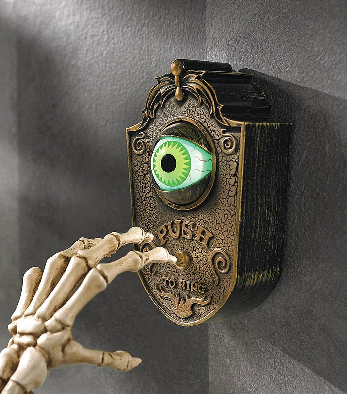 This undated photo provided by Grandin Road shows a vintage style doorbell which keeps an eye out – literally – for Halloween guests. The ghoulish green animated eyeball pops open when the button's pushed, welcoming guests with one of four greetings.(www.grandinroad.com via AP)