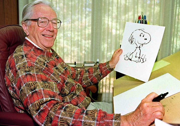 """In this Feb. 12, 2000, file photo, cartoonist Charles Schulz displays a sketch of his beloved character """"Snoopy"""" in his office in Santa Rosa, Calif. The home of """"Peanuts"""" creator Schulz burned to the ground in the deadly California wildfires but his widow escaped, her stepson said Thursday, Oct. 12, 2017. Jean Schulz, 78, evacuated before flames engulfed her hillside home Monday and is staying with a daughter, Monte Schulz said. (AP Photo/Ben Margot, File)"""