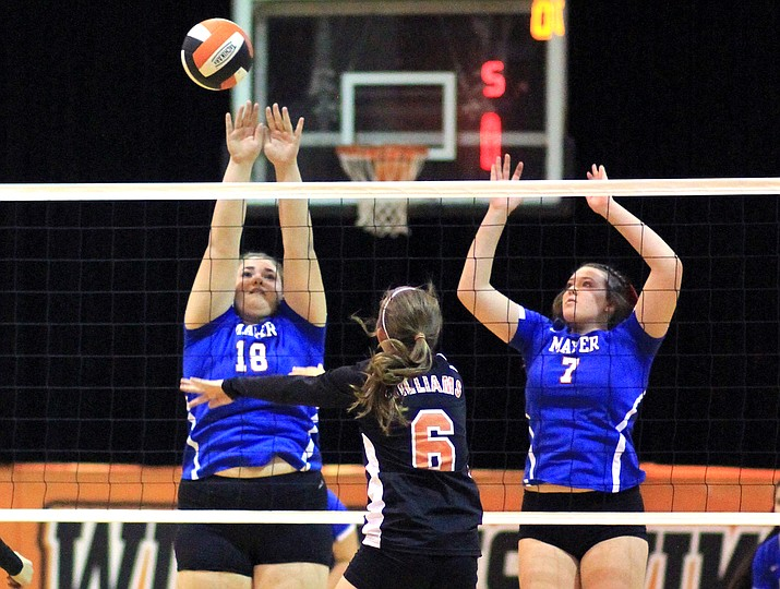 Lady Vike Maegen Ford hits the ball over two Mayer defenders.
