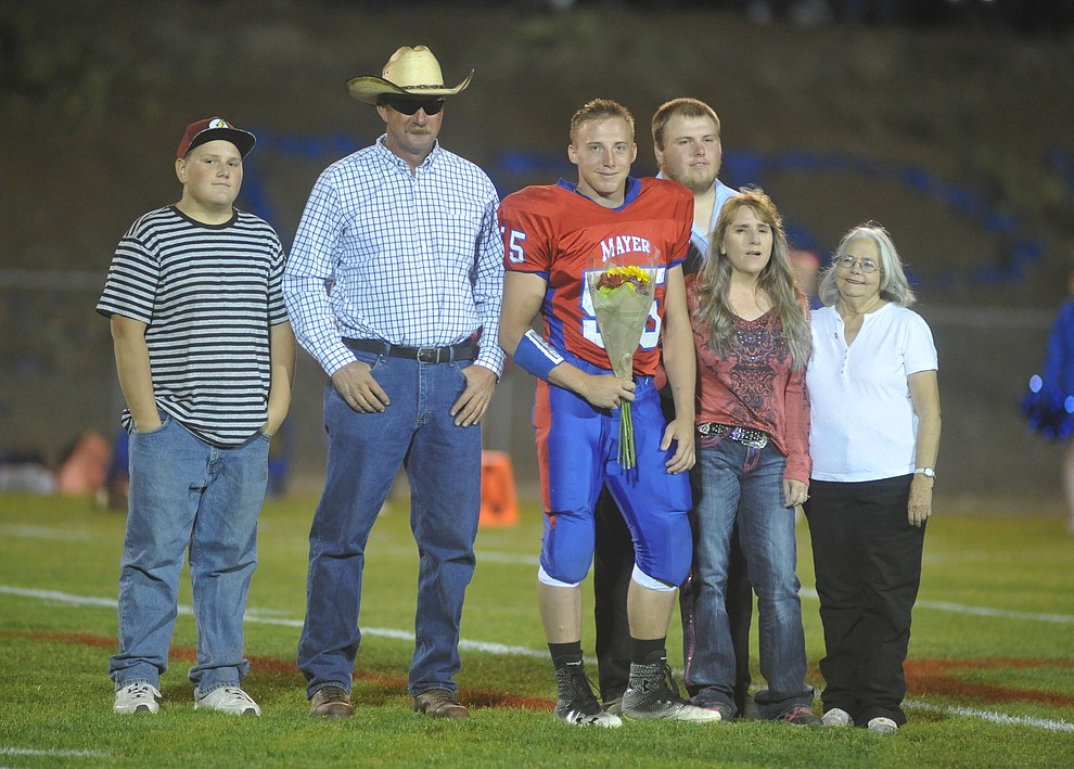 Mayer's Dacodah Jensen and his family celebrate senior night as the Wildcats faced the Bagdad Sultans Friday night in a matchup of top 4 teams in the AIA 1A rankings in Mayer. (Les Stukenberg/Courier)