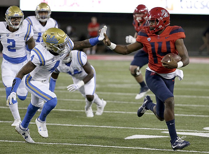 Arizona quarterback Khalil Tate (14) stiff arms UCLA defensive back Jaleel Wadood (4) and scores a touchdown in the first half Saturday, Oct. 14, in Tucson.