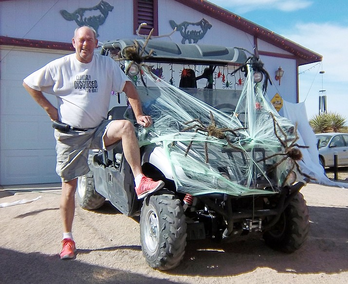 "October is not just for celebrating Halloween and passing out candy to visitors; it is also Breast Cancer Awareness Month. Retired 70-year-old U.S. Marine Gunnery Sergeant and Golden Valley resident Butch Meriwether poses wearing his pink tennis shoes next to his Yamaha Rhino that is decorated for Halloween. He says, ""It takes a big man to wear pink tennies."" He went out and purchased pink tennis shoes so he could show his support for Breast Cancer Awareness Month, an annual campaign to increase awareness of the disease. Many people don't realize men can also suffer from breast cancer. Butch says he has a friend in California who noticed he had a lump on his left breast. He went in and they did a mammogram completed and it determined he had breast cancer.  They ended up doing a mastectomy on him, which in turn, they believe saved his life because he didn't ignore the lump. Just because Breast Cancer Awareness Month is only October, an end, everyone should continue be aware of the dangers of this disease and get checkups regularly, especially if a lump is found. (Chris Marie/For the Miner)"
