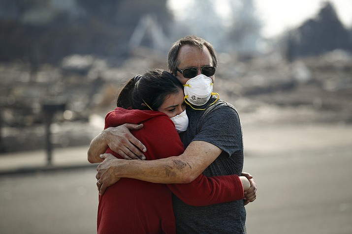 "Howard Lasker, right, comforts his daughter, Gabrielle, who is visiting their home for the first time since a wildfire swept through it Sunday, Oct. 15, 2017, in Santa Rosa, Calif. With the winds dying down, fire officials said Sunday they have apparently ""turned a corner"" against the wildfires that have devastated California wine country and other parts of the state over the past week, and thousands of people got the all-clear to return home. (Jae C. Hong/AP)"