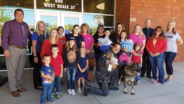 "Mohave County Sheriff Doug Schuster (at left) with administrative assistant Lydia Glentz, Chief Deputy Dean McKie (at right) and Deputy Sam Ruiz (kneeling in front row) with his K-9, Thor, were honored to pose for a picture with the children and adults from ""Cookies for a Cop and our Fire Friends."""