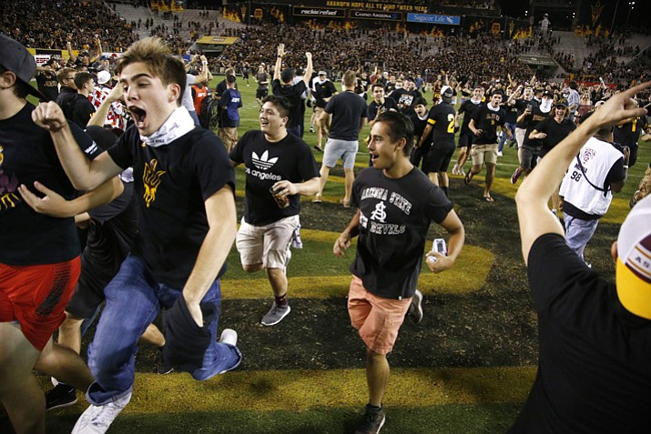 Arizona State students run on the field after an NCAA college football game win against Washington Saturday, Oct. 14, 2017, in Tempe. Arizona State defeated Washington 13-7. (Ross D. Franklin/AP)