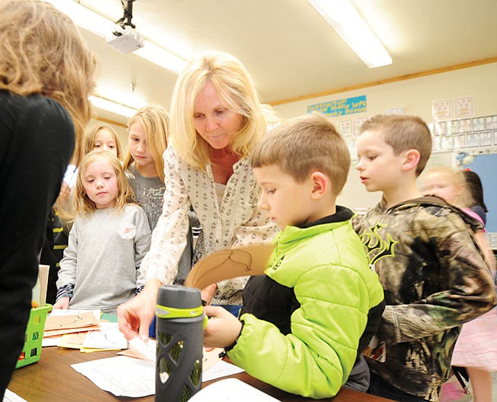 Coyote Springs Elementary School second-grade teacher Yvonne Berry hands out project materials during class. (Les Stukenberg/Courier)