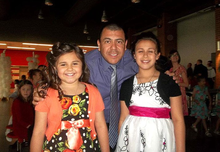Charlie Lucero smiles with his daughters Tia (left) and Paige (right) in this file photo.