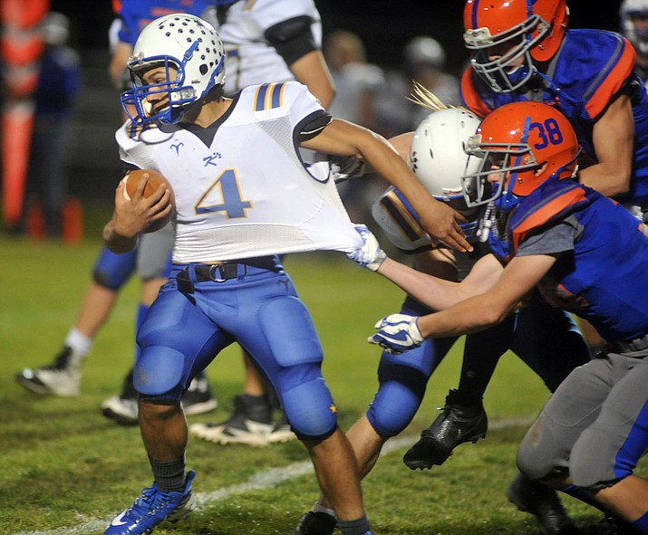 Kingman's Austin Dias tries to break a tackle earlier this season. The Bulldogs welcome River Valley to town tonight.