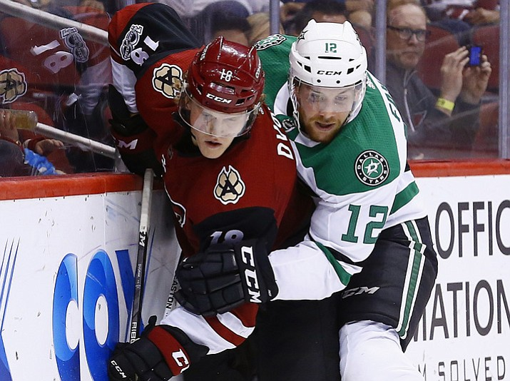 Arizona Coyotes center Christian Dvorak (18) battles with Dallas Stars center Radek Faksa (12) for the puck during the first period of an NHL hockey game Thursday, Oct. 19, 2017, in Glendale. (Ross D. Franklin/AP)