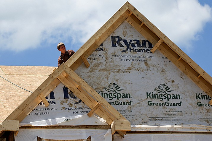 In this Thursday, June 1, 2017, photo, a builder works on the roof of a home under construction at a housing plan in Jackson Township, Butler County, Pennsylvania. On Tuesday, Oct. 17, 2017, the National Association of Home Builders/Wells Fargo releases its October index of builder sentiment. (AP Photo/Keith Srakocic)