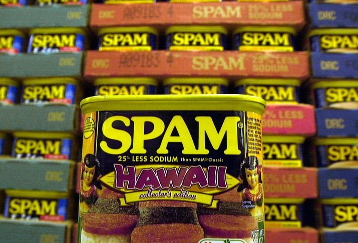 "Pictured is a collector's limited edition ""Hawaii"" can of Spam, with a hula doll on both sides of the can and a picture of three pieces of spam musubi in Kailua, Hawaii. Cans of Spam have become a common item that's being stolen from Honolulu stores and then sold on the streets for quick cash, according to authorities. The state's love affair with Spam began during World War II, when rationing created just the right conditions for the rise of a meat that needs no refrigeration and has a remarkably long shelf life (indefinitely, the company says). (AP File Photo/Lucy Pemoni, File)"