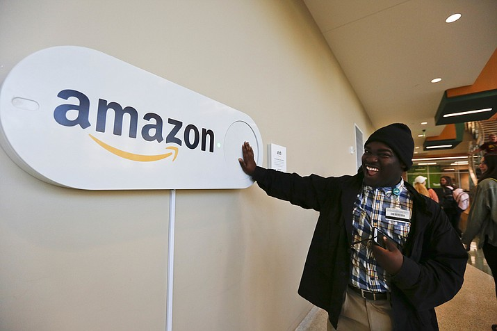 Zavian Tate, a student at the University of Alabama at Birmingham, pushes a large Amazon Dash button, in Birmingham, Ala. The large Dash buttons are part of the city's campaign to lure Amazon's second headquarters to Birmingham. (Brynn Anderson/AP)