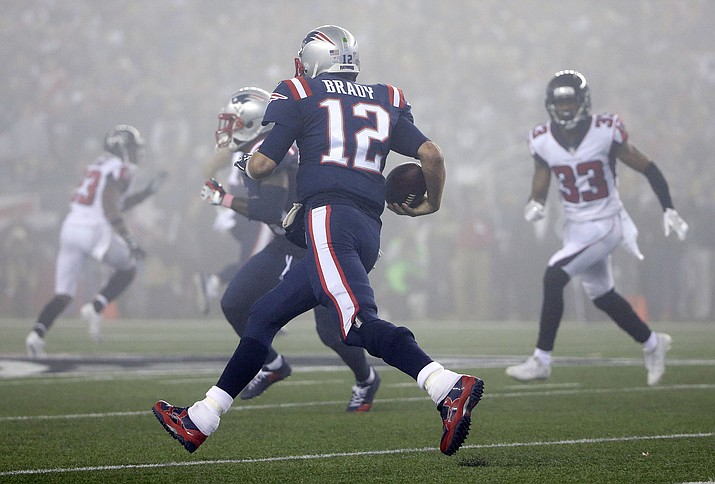 New England Patriots quarterback Tom Brady (12) runs in the fog as Atlanta Falcons defensive back Blidi Wreh-Wilson (33) pursues during the second half of an NFL football game, Sunday, Oct. 22, 2017, in Foxborough, Mass. (Steven Senne/AP)