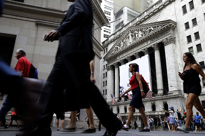 In this Monday, Aug. 24, 2015, file photo, people walk past the New York Stock Exchange. Congress is looking for ways to raise revenue, and one of the methods reportedly under consideration is to limit how much pre-tax money workers can contribute to their 401(k) and similar accounts. If it were to happen, the move would strike at a way that tens of millions of Americans use to save for retirement. (Seth Wenig/AP, File)