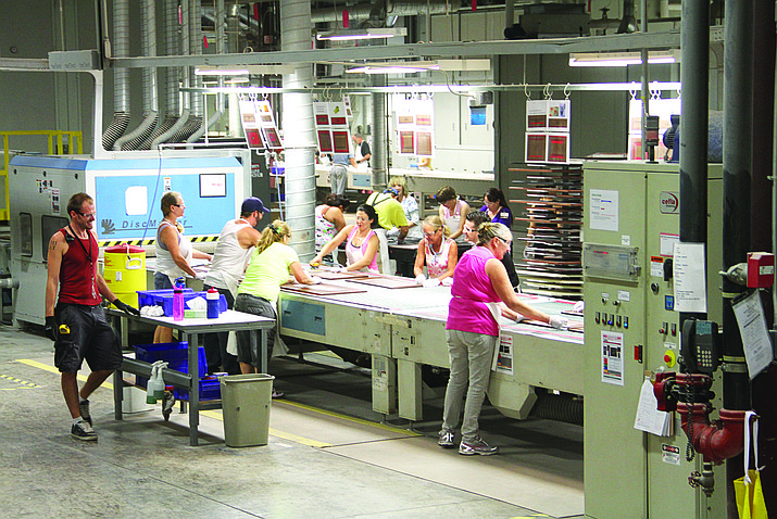 In this 2013 file photo, workers at American Woodmark help finish cabinet pieces on a conveyor belt.