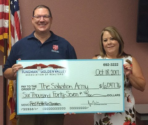 Dawn Brannies, representing the Kingman and Golden Valley Association of Realtors, presents a check in the amount of $6,047 to Salvation Army director Troy Palmer. The association raised the money at its Red Kettle Run on Sept. 30.