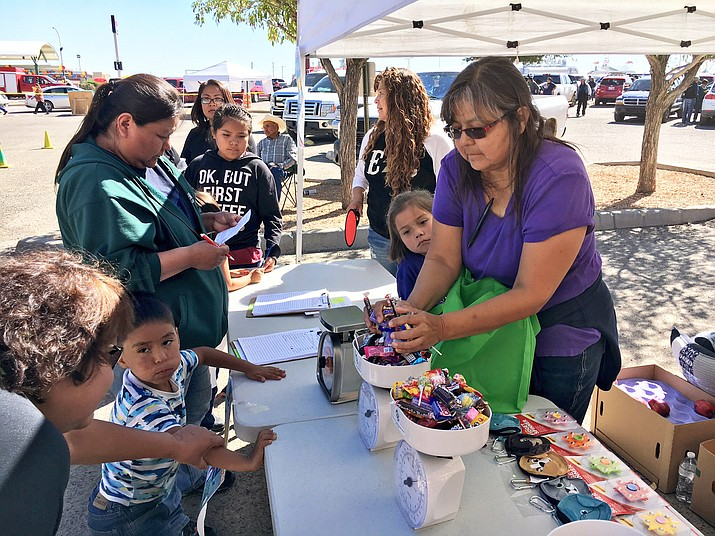 Charlene Begay (right), program supervisor for the Navajo Special Diabetes Project for the Shiprock area, weighs in over two pounds of candy brought in by a little boy (second from the left) after the parade Oct. 7 at the Northern Navajo Fair. Submitted photo
